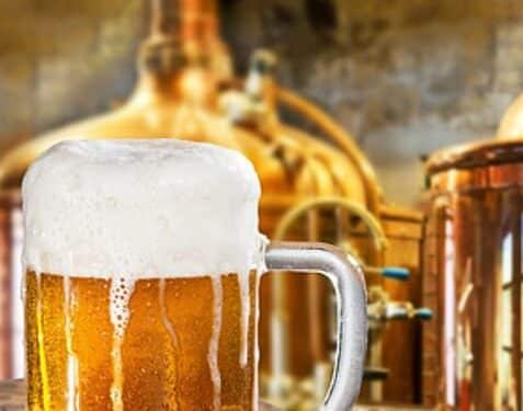 Large clear beer glass with amber beer and white froth overflowing with copper brewery equipment behind