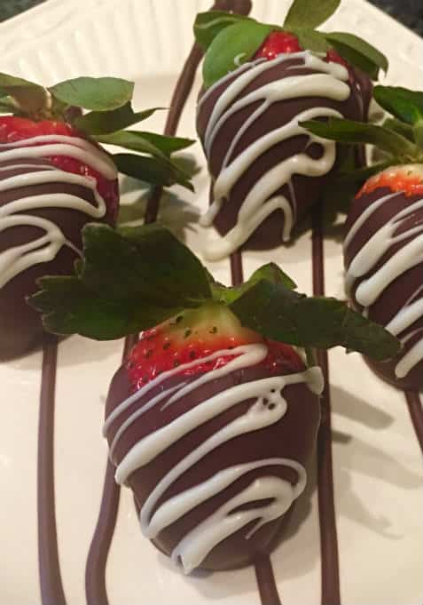 chocolate dipped strawberries with white chocolate drizzle on a plate of drizzled dark chocolate