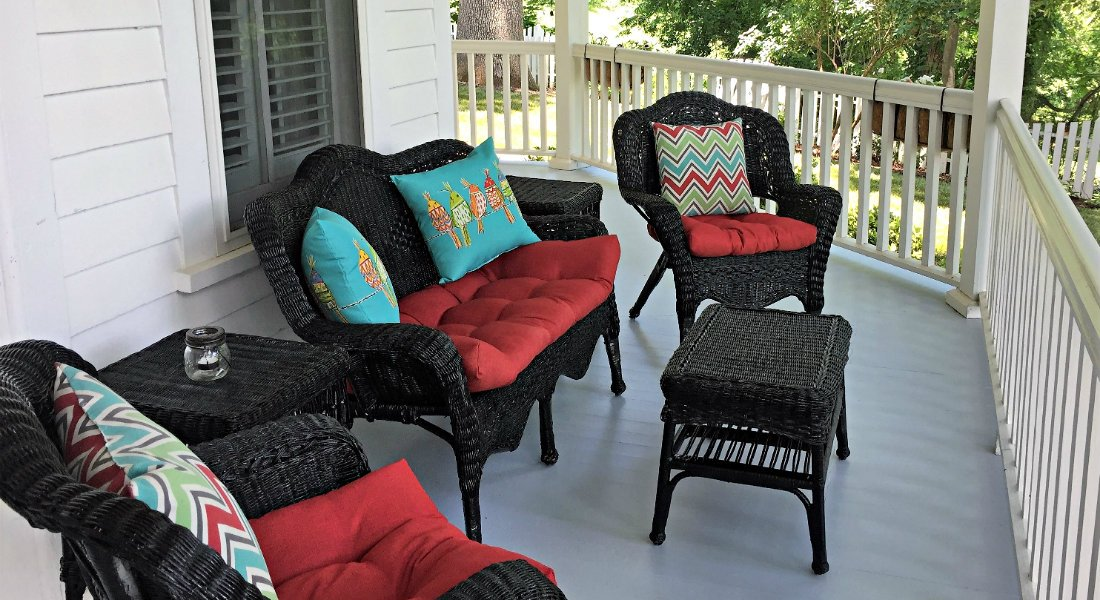 Dark wicker loveseat and two chairs with coffee and side tables, red seat cusions and vibrant multi colored pillows on outside front porch